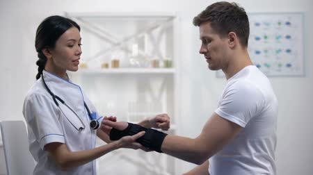 ortopedia : Kind physician applying titan wrist brace smiling male patient, rehabilitation Wideo