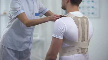 ból pleców : Orthopedist applying posture control shoulder brace male patient, healthcare