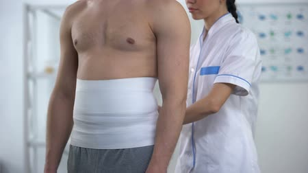 pétala : Female doctor applying back wrap male patient to decrease hypoxic tissue injury