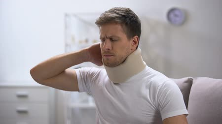 krk : Displeased man in foam cervical collar suddenly feeling pain in neck, trauma