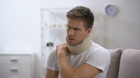 bandagem : Upset man in foam cervical collar suffering pain in back and shoulder, injury