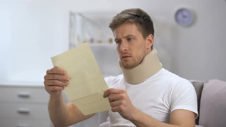 чувствовать : Man in foam cervical collar reading medical bill shocked with high price, health