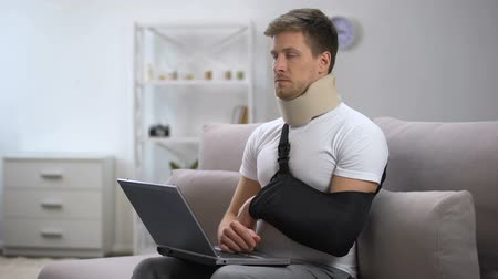 bandagem : Injured man in foam cervical collar and arm sling working on laptop feeling pain