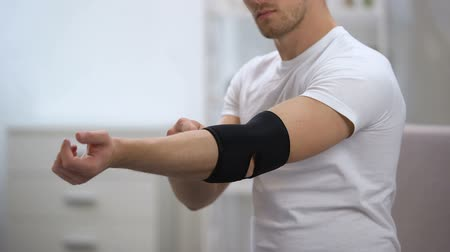 cotovelo : Young male applying elbow padded orthosis, trying to move hand, orthopedics
