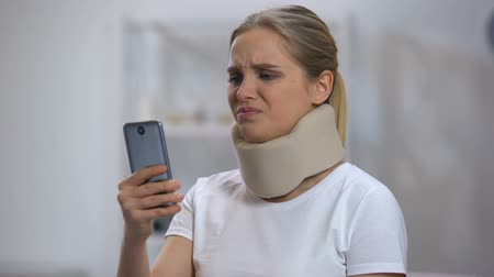 bandage : Woman in foam cervical collar reading message on cellphone, feeling pain in neck