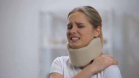 coleira : Upset girl in foam cervical collar suffering pain in back and shoulder, injury Vídeos