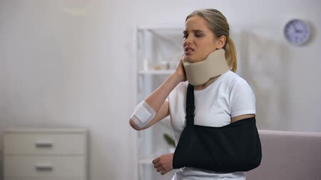ortopedia : Injured woman in foam cervical collar and arm sling suffering pain in neck rehab