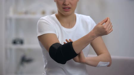 артрит : Woman applying elbow padded orthosis, feels pain after sport injury, orthopedics