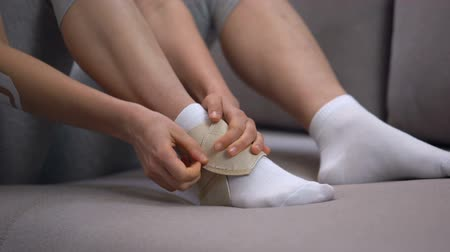 kotník : Lady fixing two-strap ankle wrap in proper position anti-inflammatory medication
