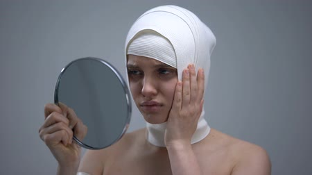 bandage : Female in elastic headwrap looking in mirror, feeling pain after plastic surgery Stock Footage