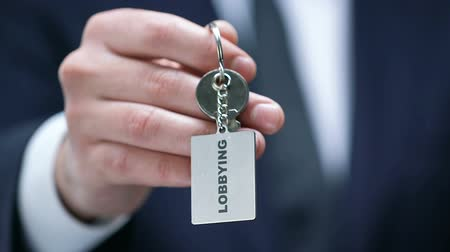 persuasion : Lobbying word on keychain in male politician hand, governmental influence