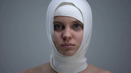 wrapped up : Female patient in headwrap looking to camera, rehabilitation after car accident