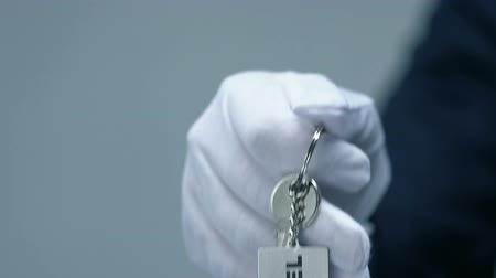 szállás : Hotel word on keychain in male doorman hand, friendly luxury resort service