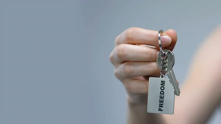 anti war : Woman clenching keychain with freedom word in fist, discrimination protest