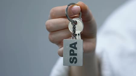 szállás : Woman clenching keychain with spa word in fist, beauty procedure, wellness
