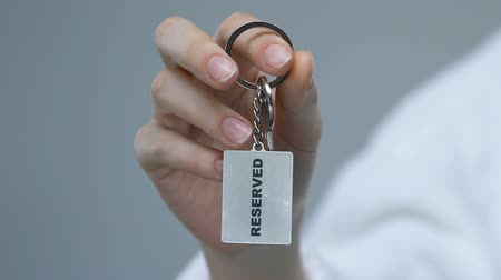 odemknout : Female hand clenching keychain with reserved word, luxury hotel service, trip