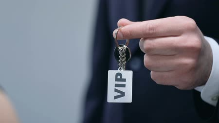 doorway : Man presenting woman keychain with VIP word, luxury service for rich people