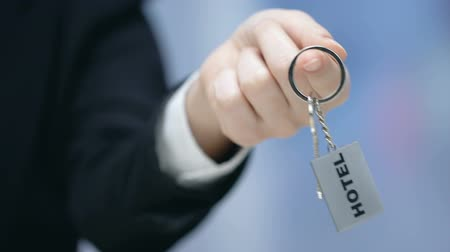 proposing : Hotel word on keychain in female administrator hand, friendly stuff, service
