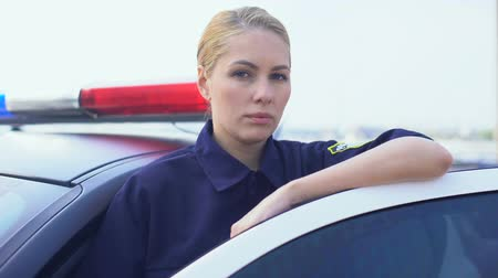 squad car : Brave policewoman standing near patrol car, protection of public order in city Stock Footage