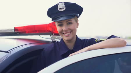 policista : Strong woman in police uniform standing near patrol car smiling, law and order