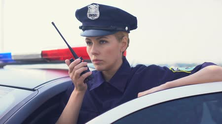 politievrouw : Serious police woman receiving call on radio set, getting into car and rushing