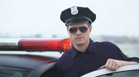 охранять : Confident police officer in uniform and sunglasses standing near patrol car