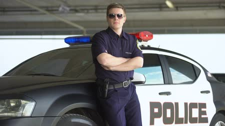 squad car : Armed policeman in sunglasses standing near patrol car, dangerous profession Stock Footage