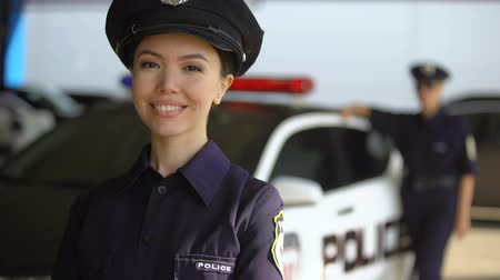 squad car : Smiling asian policewoman posing to camera against partner near patrol car, duty Stock Footage