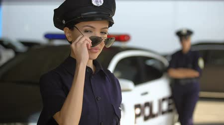 squad car : Beautiful patrolwoman taking off sunglasses and smiling near police car