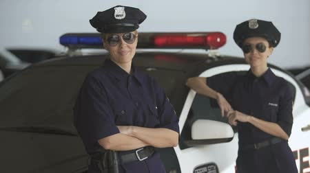 squad car : Two women in police uniform standing near patrol car and smiling, law and order