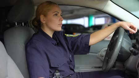 zsaru : Tired policewoman taking off service cap sitting in patrol car, night shift