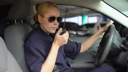 politievrouw : Professional police officer taking call on radio set and driving to crime scene Stockvideo
