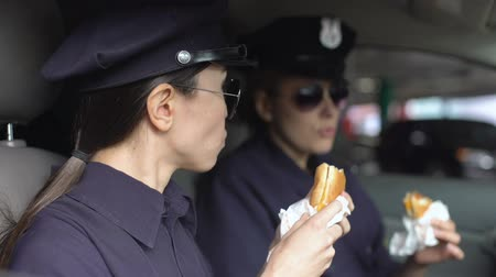 poliziotta : Policewomen on duty having lunch, eating burgers in patrol car, unhealthy diet