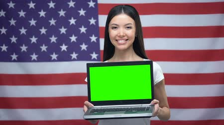 nativo americano : Woman holding laptop with green screen, USA flag on background, language lessons