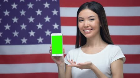 nativo americano : Girl showing smartphone with green screen, US flag on background, translator app