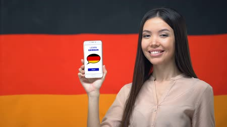 grãos : Female showing cellphone with learn German app, flag on background, education