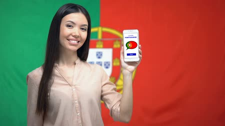grãos : Girl showing cellphone with learn Portuguese app, flag on background, education