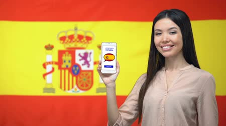 derece : Girl holding smartphone with language study app, Spanish flag on background