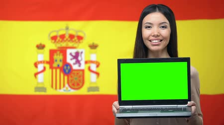 průvodce : Female student holding laptop with green screen, Spanish flag on background
