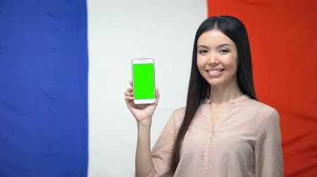 traductor : Lady showing smartphone with green screen, French flag on background, travel app
