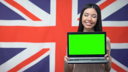 aluno : Female showing laptop with green screen against British flag background, study Stock Footage