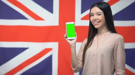 talk show : Lady showing phone with green screen against British flag on background, app Stock Footage