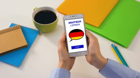 külföldi : German language application on smartphone in persons hands, online education Stock mozgókép
