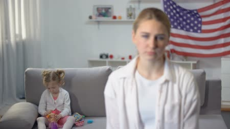 kusy : Sad single mother looking at camera daughter playing on sofa against flag of USA