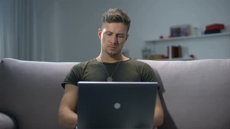 freelance work : Male soldier typing on laptop pc at home, communication concept, military app Stock Footage