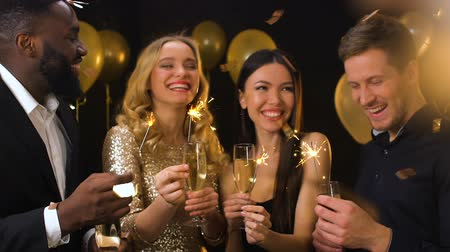 bengália : Smiling multiracial couples with champagne glasses and bengal lights, party Stock mozgókép