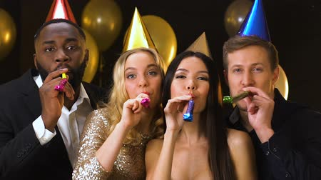doğum günü : Happy multiracial friends in b-day hats blowing in party ticklers, celebration Stok Video