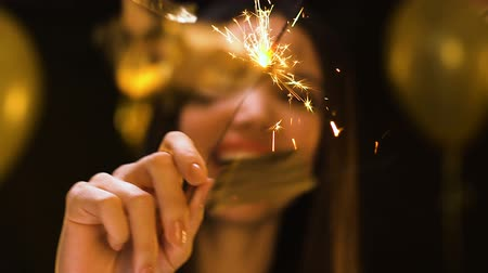 lights up : Smiling Asian woman showing bengal light to camera, New Year corporate party Stock Footage