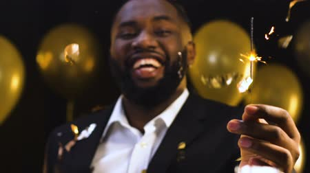 sending : Black man showing bengal light to camera under falling confetti, New Year party Stock Footage