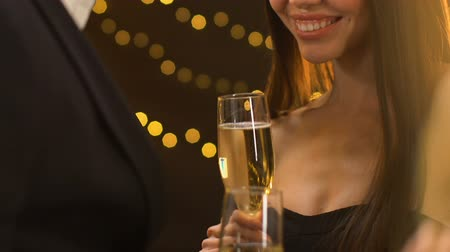 seduce : Smiling seductive lady holding glass with champagne and flirting with man, party Stock Footage